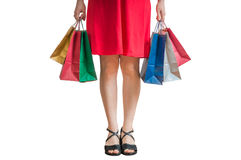 Shopping and consumerism concept. Legs of young woman holding shopping bags. Isolated on white background Stock Photos