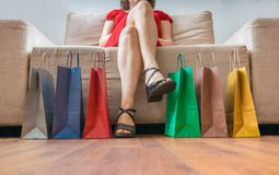 Shopping and consumerism concept. Legs of young woman sitting on sofa. Shopping and consumerism concept. Legs of young woman sitting on sofa and many colorful Stock Images