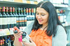 Shopping and consumerism concept. Smiling happy young woman choosing wine in market or liquor store.  stock image