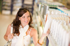 Shopping cosmetics - smiling woman choose shampoo Royalty Free Stock Photo