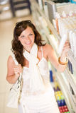 Shopping cosmetics - smiling woman choose shampoo Stock Image