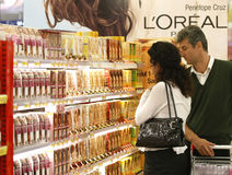 Shopping for cosmetics at supermarket - L'oreal. Customers shopping for L'Oreal cosmetics between the shelves, in the aisle inside a supermarket