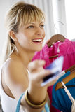 Shopping with credit card. Young woman clothes-shopping with credit card Stock Photography