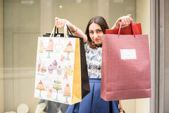 Shopping Day. Beautiful brunette girl holding big colorful shopping bags in front of a window of a store in the city mall, Enjoying her day buying new clothes Stock Photos