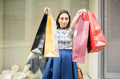 Shopping day. Beautiful brunette girl holding big colorful shopping bags in front of a window of a store in the city mall, Enjoying her day buying new clothes Stock Images
