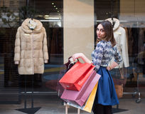 Shopping Day. Beautiful brunette girl holding big colorful shopping bags in front of a window of a store in the city mall, Enjoying her day buying new clothes Stock Photography