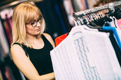 Shopping day. Beautiful young woman shopping in clothing store. Toned photo, added film grain Royalty Free Stock Photo