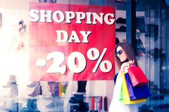 Shopping day. Beautiful young woman outdoors with plenty of shopping bags. Portrait of young shopaholic woman in trendy clothes with surprise face as she see a Stock Photo