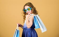 Shopping day. Child fashion girl sunglasses hold package. Favorite kids brand. Girl with shopping bag. Shopping tour. Abroad. Summer season sale. Shopping and stock photos