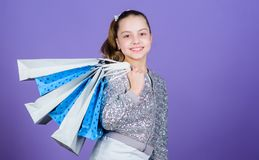 Shopping day. Child hold bunch packages. Kids fashion. Birthday girl. Favorite brands and hottest trends. Girl with. Shopping bags violet background. Shopping royalty free stock photography