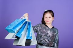 Shopping day. Child hold bunch packages. Kids fashion. Birthday girl. Surprise gift. Girl with shopping bags violet. Background. Shopping and purchase. Get royalty free stock image