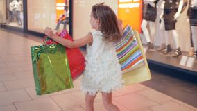 Shopping day, happy child girl with packages into hands runs through shopping center after buy in fashion boutiques. In season of discounts stock footage