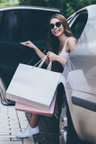 Shopping day is just starting. Beautiful young smiling woman carrying shopping bags and opening door car door while sitting inside of it Stock Photography