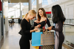 Shopping day. Three women are in mall after shopping. They take their shopping bags and look in it. Girls are happy. Seeing what is there Royalty Free Stock Photo