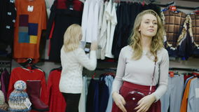 Shopping in the department of accessories. Young woman watching a red bag: in the background other buyers stock footage