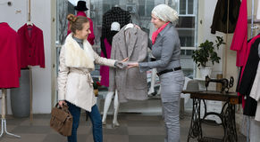 Shopping at Department Store Customer and Saleslady interacting. Customer selecting Jacket at Clothing Department Store talking with Saleslady who explains Royalty Free Stock Images