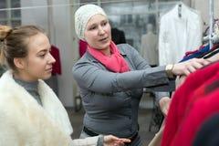 Shopping at Department Store Customer and Saleslady interacting. Customer selecting Jacket at Clothing Department Store talking with Saleslady who explains Stock Image