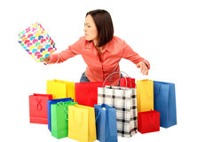 Shopping Desaster. Brunette woman sitting in the middle of colored shopping-bags royalty free stock photography