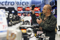Shopping for digital photo cameras in supermarket. A customer analyzes a SLR body at the digital photo cameras sale department inside a supermarket royalty free stock image