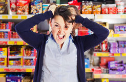 Attractive woman yelling or screaming in grocery s. Attractive young woman pulling her hair, screaming or yelling, going crazy about shopping in grocery store Royalty Free Stock Image