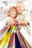 Shopping elderly people. Happy shopping elderly people in the mall Royalty Free Stock Images