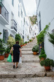 An elderly woman carrying home shopping up steep steps Royalty Free Stock Photo