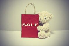 Shopping för nallebjörnen och för den pappers- påsen skriver ordförsäljningen tappning för stil för illustrationlilja röd royaltyfria foton