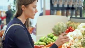 Shopping för ung kvinna i livsmedelsbutik Stå i grönsakavdelningen som väljer den nya kronärtskockan lager videofilmer