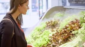 Shopping för ung kvinna i livsmedelsbutik Stå i grönsakavdelningen som väljer ny grön sallad arkivfilmer