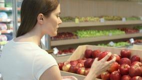 Shopping för ung kvinna i livsmedelsbutiken för sund mat Strikt vegetarianflicka som väljer nya röda äpplen arkivfilmer