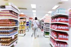 Shopping för ung kvinna i supermarket Fotografering för Bildbyråer