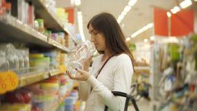 Shopping för ung kvinna för möblemang, exponeringsglas, disk och hem- dekor i lager arkivfilmer