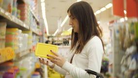 Shopping för ung kvinna för möblemang, exponeringsglas, disk och hem- dekor i lager stock video