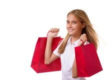 Shopping, försäljning, jul och ferie-älskvärd ung flicka med röda shoppingpåsar som isoleras Royaltyfri Fotografi