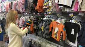 Shopping family. Woman buying clothes child. Young woman choosing clothing for girl kids in the hypermarket. Children`s. Goods store. Woman looking for clothes stock footage