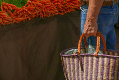 Shopping at farmers market. Man shopping at farmers market with woven basket and carrots Royalty Free Stock Photos