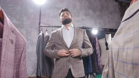 Shopping and fashion concept - Young bearded man choosing and trying jacket on in mall or clothing store. Shopping and fashion concept - Elegant young bearded stock video footage