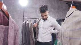 Shopping and fashion concept - Young bearded man choosing and trying jacket on in mall or clothing store. Shopping and fashion concept - Elegant young bearded stock footage