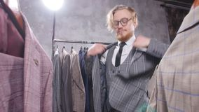 Shopping and fashion concept - Young bearded man choosing and trying jacket on in mall or clothing store. Shopping and fashion concept - Elegant young bearded stock video