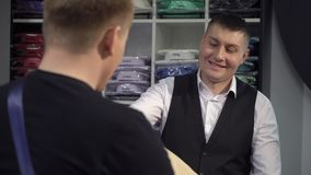 Shopping and fashion concept - young man choosing and trying jacket on in mall or clothing store.  stock video footage