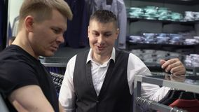 Shopping and fashion concept - young man choosing and trying jacket on in mall or clothing store.  stock video
