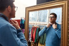 Man looking at mirror at vintage clothing store. Shopping, fashion and sale concept - man or hipster choosing clothes and looking at mirror at vintage clothing Stock Image