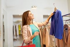 Happy woman choosing clothes at clothing store stock photography