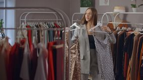 Shopping, fashion, style and people concept - happy woman choosing clothes and looking to mirror in mall or clothing