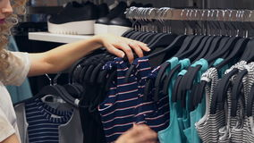 Shopping, fashion, style and people concept. Shopping women choosing dress in mall or clothing store stock footage