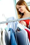 Shopping female. Portrait of charming girl looking at shirt in clothing departmant Stock Photography