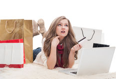 Shopping female holding card and thinking Stock Images