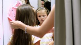 Shopping. in fitting room of large store, pretty, serious girl, a kid tries on new outfits, chooses what to buy. The stock video