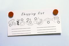 Shopping food list with magnets. White fridge background Royalty Free Stock Photography