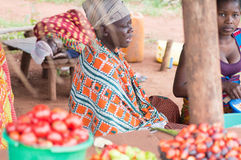 Shopping for food products. Akoupé, Cote d'Ivoire- August 20, 2015: the sellers of food products are installed under a shed for sale Royalty Free Stock Image